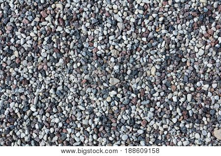 Small gray stones on a ground natural material background