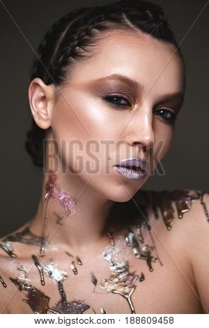Beautiful strange girl with creative art make-up. Beauty face. Photo taken in studio