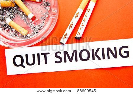Quit Smoking - health and money - with cigarettes, ashtray and printed words on red background