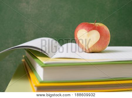 Apple On Stack Of Books Next To A Chalk Board