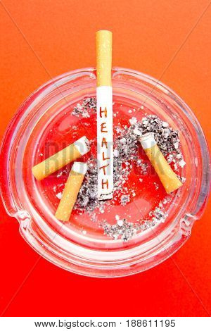 Quit Smoking - Health with cigarette and ashtray on red background