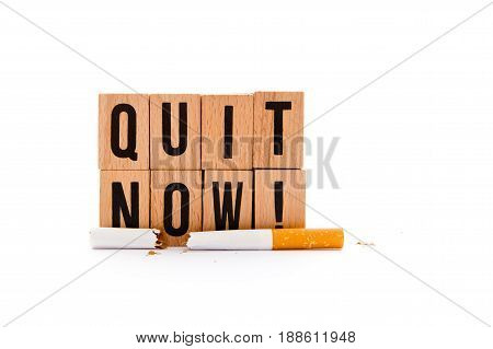 Quit Now - block wooden letters with broken cigarette on white background