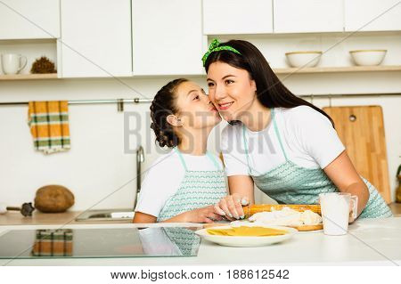 Happy daughter kissing mother during cooking at home, spending time with family