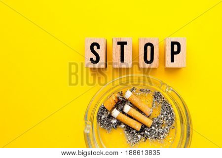 Stop Smoking - block wooden letters with ashtray on yellow background