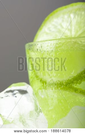 A Glass Of Lemonade With Lime On Ice