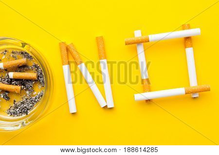Quit Smoking - No in cigarettes with ashtray on yellow background