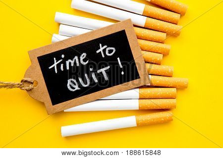 No Smoking - Time to Quit - with cigarettes and handwritten blackboard on yellow background