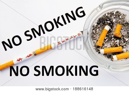 No Smoking - with cigarettes and ashtray with printed words on blue and white background