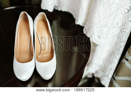 Elegant stylish white wedding shoes on wooden table with a dress in background. Morning preparetion.