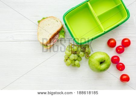 school lunch set with apple and vegetables in lunchbox on white wooden table background top view mock up
