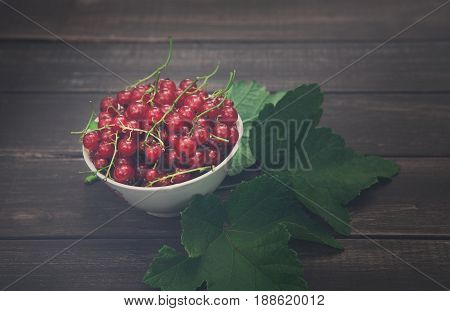 Fresh ripe red currants on rustic wood background. Bowl with natural ripe organic berries with peduncles and green leaves on old weathered grey wooden table, closeup of new berry harvest