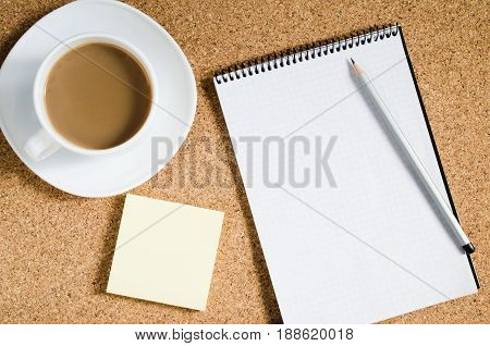 Top view image of empty notebook blank notes next to cup of coffee on cork board. Ready for adding text or mockup. Flat lay.
