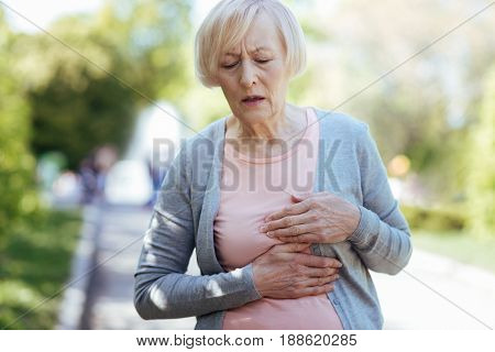 My weak heart . Concentrated old ill woman touching her chest and expressing sadness while suffering from heart attack outdoors
