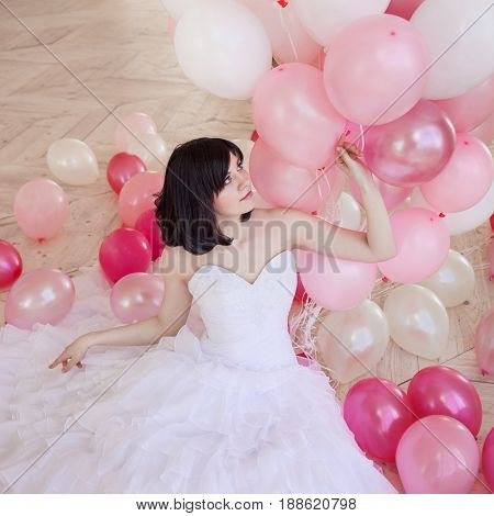 Young woman in wedding dress in luxury interior with a mass of pink and white balloons, sitting on the floor. Charming young bride brunette with short haircut in stylish Quinceanera dresses.