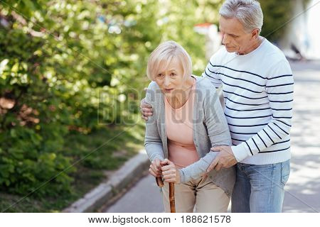 Never left you without my support. Attentive loving aging man caring about his aged wife and helping her to make steps while hugging woman and walking in the park