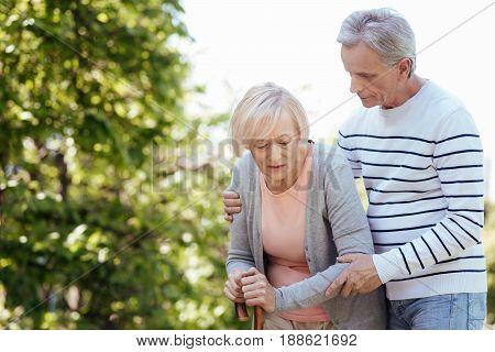 Always close to you for help. Helpful caring kind man caring about his aged wife and helping her to make steps while walking in the park