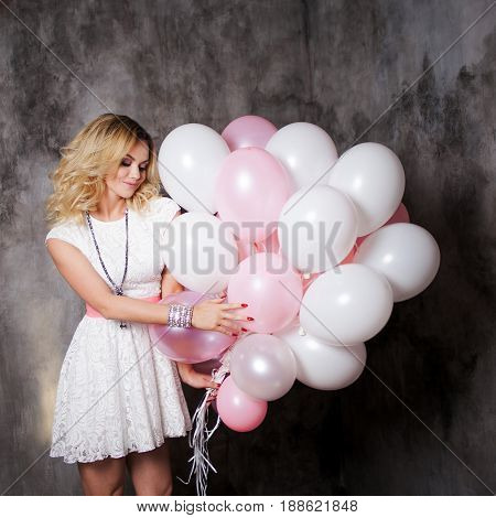 Charming young blonde in a white dress with pink sash, holding a large bundle of balloons. Happy and cheerful girl with balloons. On gray textured background