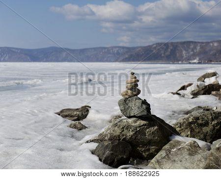 Stone tower on ice winter background. Baical landscape