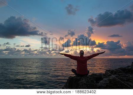 Woman (or man) sits as yogi with outstretched hands and contemplates beautiful sunset over sea.