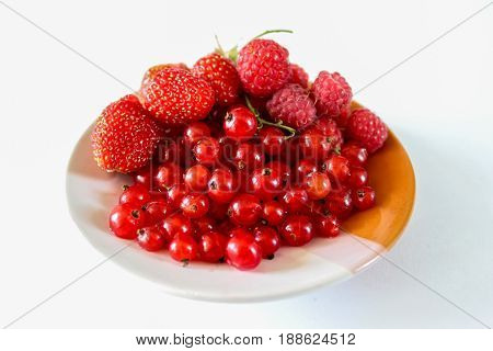 Ripe red berries on a plate. Berries of strawberries raspberries and currants. Close-up. Sweet and juicy berries on a white background.