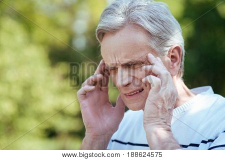 Problems with blood pressure. Elderly puzzled sad man touching his temples and expressing frustration while suffering from headache outdoors