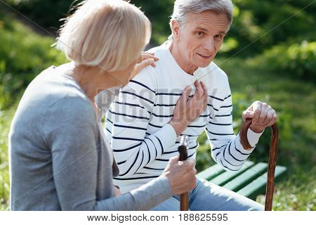 Worrying about my love. Supportive elderly ill couple feeling bad and supporting each other while holding sticks and sitting on the bench outdoors