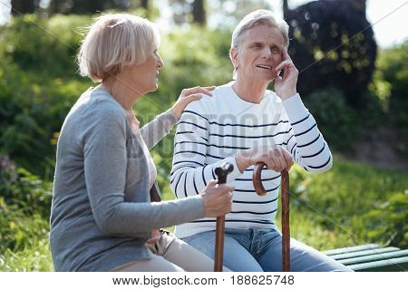 Take a deep breath. Aged concentrated helpful couple feeling bad and supporting each other while suffering from headache and sitting in the park