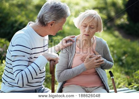 Feeling bad again. Sad depressed old woman touching her chest and having heart attack while her aged husband worrying about her and sitting on the bench outdoors