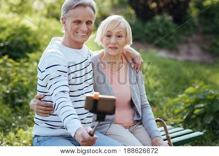 Our first selfie. Smiling delighted old couple hugging each other and using selfie stick while enjoying weather in the park and taking pictures