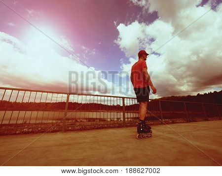 Vintage Tone Filter Effect Color Style. Sportsman  With Inline Skates Ride In Summer Park