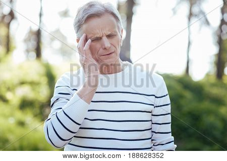 Feeling killing pain . Frustrated retired upset man touching his head and feeling strong pain while walking in the park