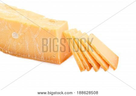 Several thin slices of the Dutch hard cheese Beemster on a dark glass saucer and piece of the same cheese beside on a light background