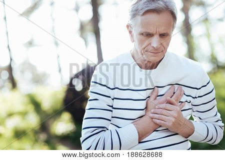 Having troubles with my weak heart. Puzzled handsome old man touching his chest and feeling pain while sitting outdoors