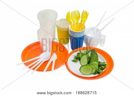 Orange and white disposable plastic plate with whole and sliced cucumber disposable forks spoons and knifes paper and different plastic disposable cups beside on a light background
