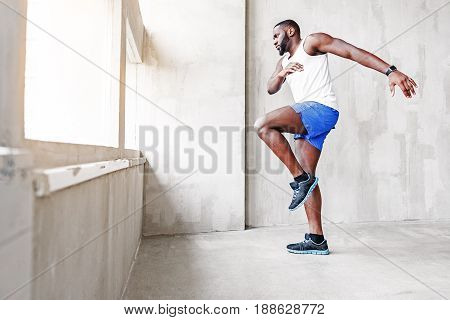 Depression concept. Despondent african bearded sportsman is taking run to jump out window