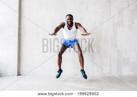 Full length portrait of young man performing leap upwards. Muscular guy is freezing in air stretching his hands forward and bending his knees. He is expressing intension