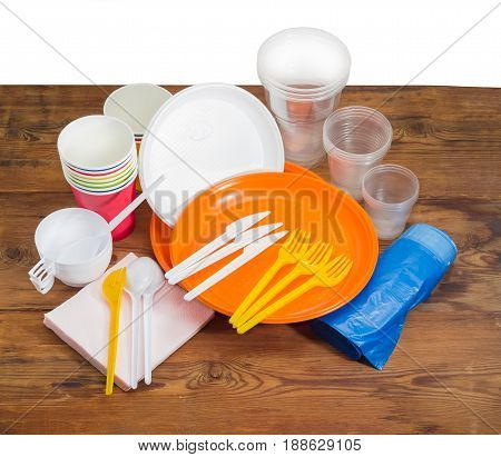 Different disposable plastic and paper cutlery paper napkins and roll of disposable garbage bags on the old wooden planks