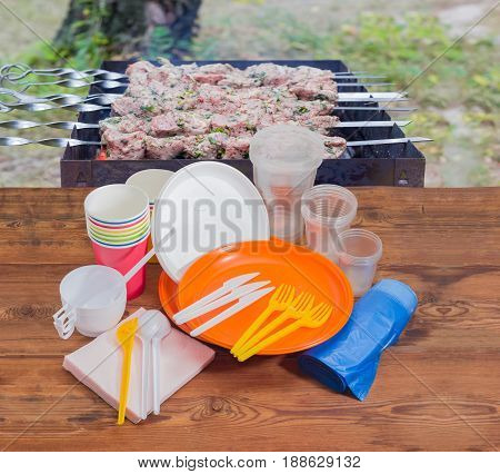 Different disposable plastic and paper cutlery paper napkins and roll of disposable garbage bags on the old wooden planks against the background of charcoal grill with grilled skewered meat outdoors