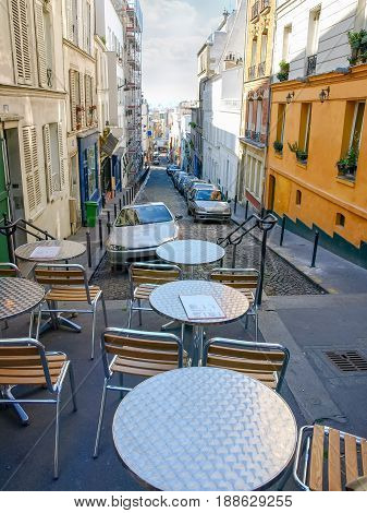 Narrow steep street with tables of the sidewalk cafe in the foreground on the Montmartre hill in Paris France