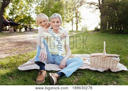 Enjoying family weekend. Happy loving aged couple expressing delight while hugging and enjoying picnic outdoors