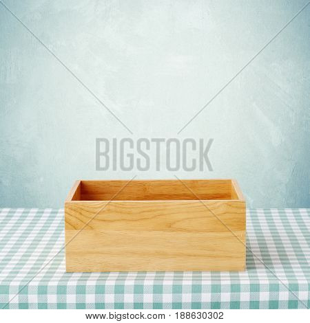 Empty wooden storage box on table with green checked tablecloth over green wall background product display montage