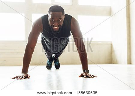Happy bearded athlete is easily making front plank. He is smiling broadly and lying in push-up position