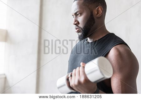 Pensive bearded athlete is lifting hand weights and looking far away. Copy space in left side