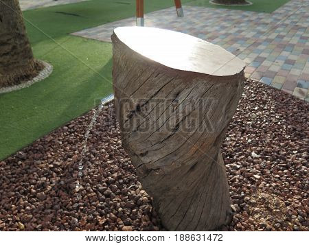 Wooden stump drinking fountain in childrens playground in andalusian village