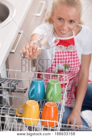 Woman Holding Wine Glass Above Dishwasher