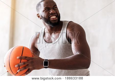 Half length portrait of furious african athlete with basketball. He is going to make perfect pitch