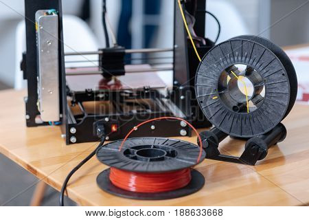 Necessary detail. Close up of a red 3D printer filament lying on the table while being ready for usage