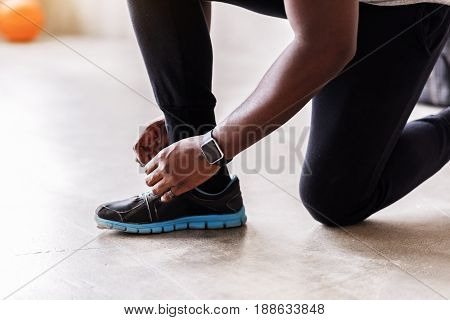 Serious mature african sportsman is going to start his training. He is fixing his shoelaces. Close up of athletic shoe and sport watch