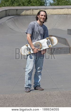 a skateboarder hunk posing with his board