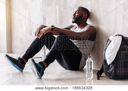Tired handsome athlete is sitting on floor and leaning on wall. Focus on bottle of water